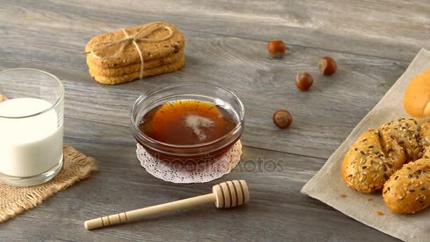 Med, mléko, soubory cookie a čerstvé bagety na rustikální dřevěný stůl. Krajina se snídaní