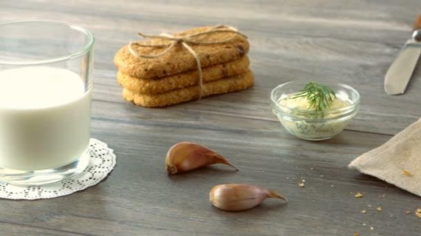 Mléko, máslo, cookies a čerstvé bagety na rustikální dřevěný stůl. Krajina se snídaní