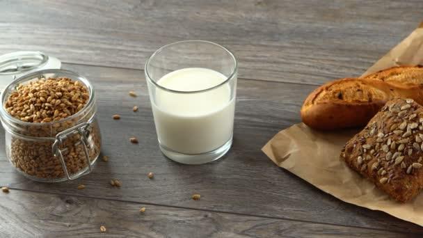 Čerstvé domácí bagety, mléčné a pšeničné zrno na rustikální dřevěný stůl. Přirozené a zdravé stravování