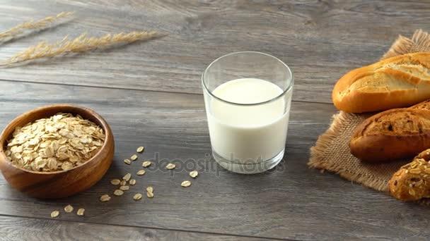 Ovesné vločky v misce, sklenici mléka a čerstvé domácí bagety na rustikální dřevěný stůl