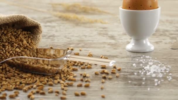 Pytel pšenice, vajec, másla a čerstvé bagety na rustikální dřevěný stůl. Krajina se snídaní