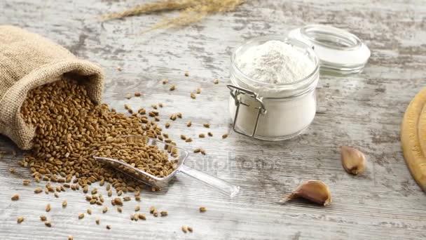 Pytel pšenice, mouka, česnek a čerstvé bagety na rustikální dřevěný stůl