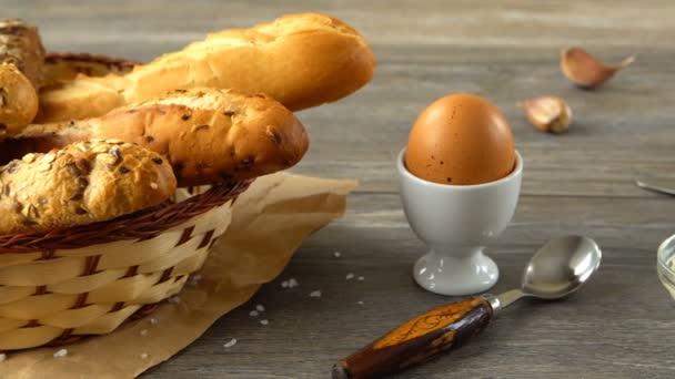 Mléko, máslo, sušenky, vejce a čerstvý chléb na rustikální dřevěný stůl. Krajina se snídaní