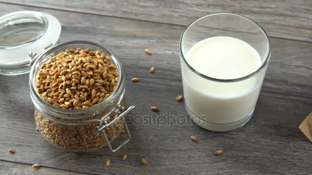 Čerstvé domácí bagety, pšeničného zrna a mléka na rustikální dřevěný stůl. Přirozené a zdravé stravování