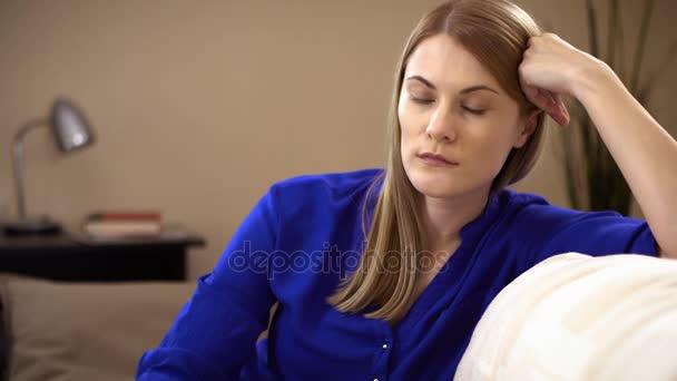 Smutné, depresivní mladá žena sedí na pohovce. Negativní emoce a pocity koncepce