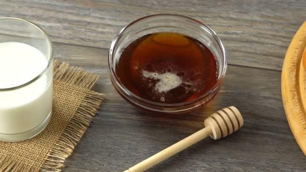 Med, mléko a čerstvé bagety na rustikální dřevěný stůl. Krajina se snídaní