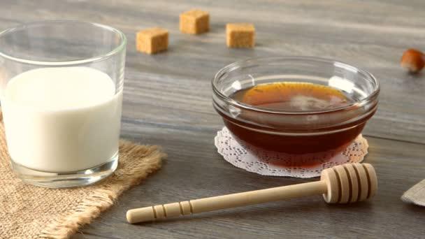 Mléko, med a čerstvé bagety na rustikální dřevěný stůl. Krajina se snídaní