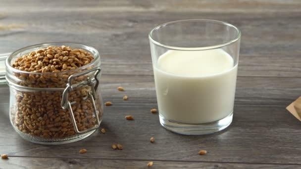 Čerstvé domácí bagety, mléko a jar pšenice na rustikální dřevěný stůl. Přirozené a zdravé stravování