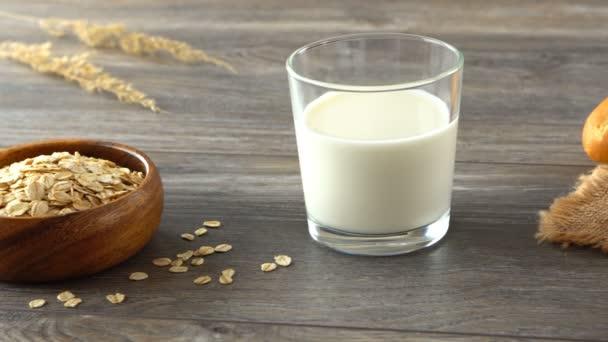 Sklenice mléka, misku ovesných vloček a čerstvé domácí bagety na rustikální dřevěný stůl