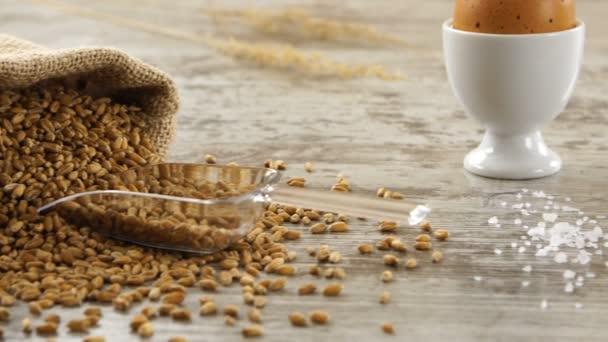 Pytel pšenice, vajec, másla a čerstvý chléb na rustikální dřevěný stůl. Krajina se snídaní