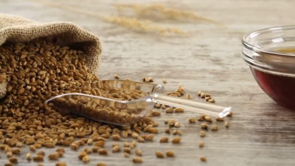 Pytel pšenice, medu a čerstvé bagety na rustikální dřevěný stůl. Krajina se snídaní