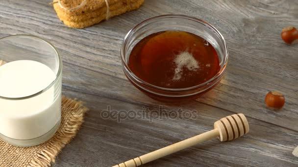 Mléko, med, soubory cookie a čerstvé bagety na rustikální dřevěný stůl. Krajina se snídaní