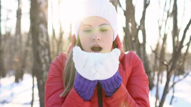 Beautiful young woman blowing snow in a winter park, having silly fun, smiling. Slow motion.