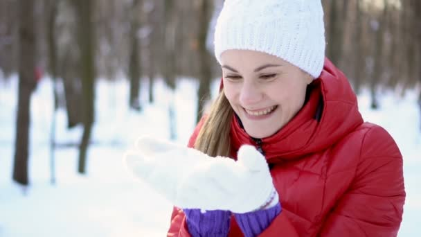 Attractive young woman blowing snow in winter park, having silly fun, smiling. Slow motion.
