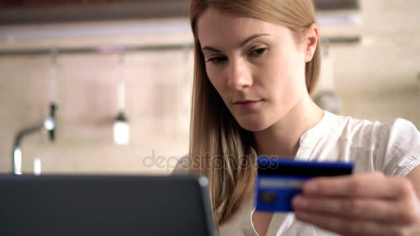 Gyönyörű vonzó fiatal nő vásárol online hitelkártyával a laptopon. Konyha.