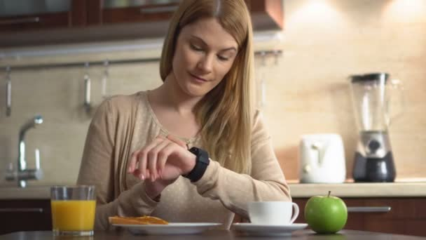 Beautiful young woman making various gestures with her finger on a touch screen of her smart watch.