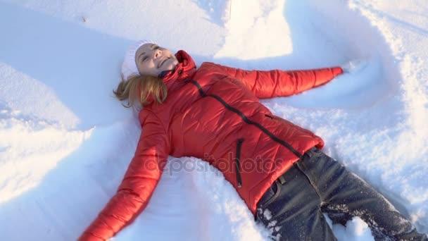 Vonzó fiatal nő így hó angyal egy téli Park, ostoba szórakozás, mosolyogva. Lassú mozgás.
