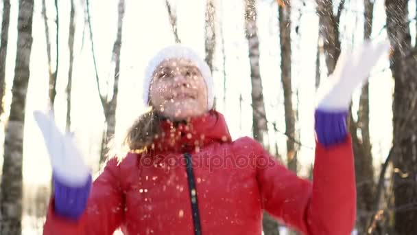 Beautiful young woman in a sunny winter park, playing with snow, having fun, smiling. Slow motion