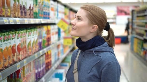 Krásná přitažlivá žena, volba balené džusy v supermarketu. Vezměte si balení z police, číst etikety