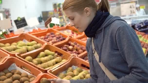 Krásná atraktivní mladá žena vybírala Kiwi ovoce v supermarketu. Zdravé stravovací koncept