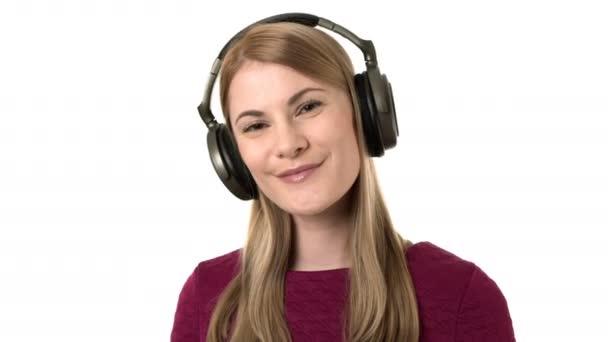 Krásná žena s sluchátka poslouchá hudbu na smartwatch. Posílá pusu rukou. Izolovaný.