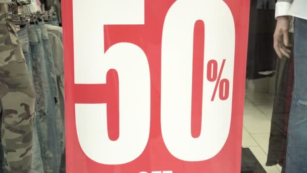 Big red sales sign in a shop window. 50 percent sales. Promotion. Consumerism concept.