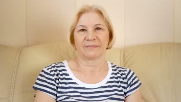 Vidám szép magas rangú nő ül a kanapén, otthon portréja. Jó idő pihentető.