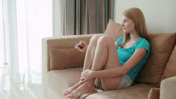 Nádherný atraktivní žena sedí na pohovce a sledování filmu. Přepínání kanálů s dálkovým ovládáním