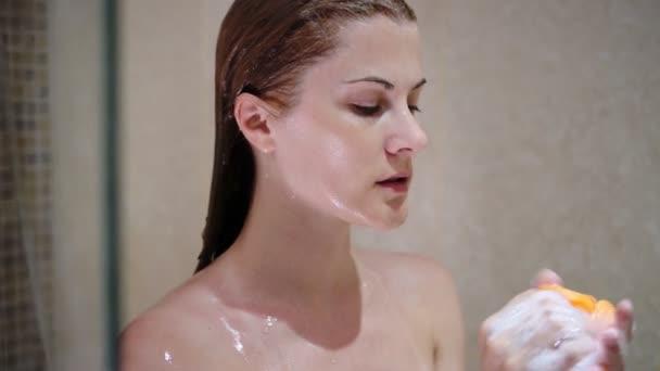 Krásná atraktivní mladá žena osprchování. Dívka praní s pěnitou houba bath. Tekoucí vody
