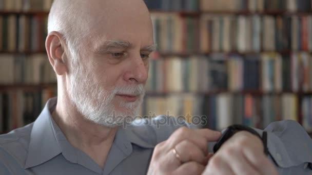 Moderní starší muž doma pomocí hodinek smartwatch, diktování zpráv. Knihovna knihovna v pozadí