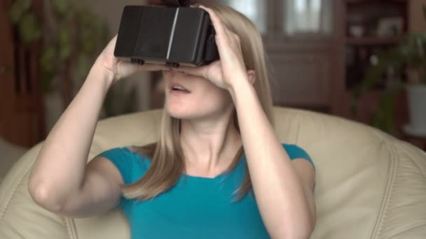 Moderní neformální žena v modrém tričku sedící v křesle doma. Pomocí virtuální reality brýle