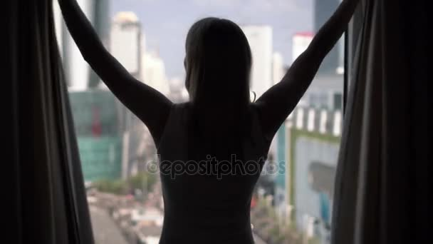 Silhouette of woman unveiling curtains, looking out of window and stretching. City skyscrapers landscape outside