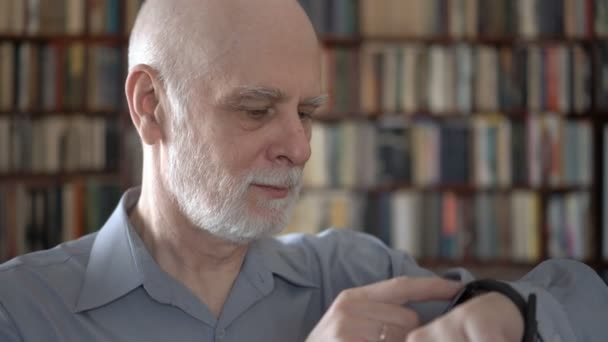 Modern senior man at home using smartwatch, browsing, reading. Bookcase bookshelves in background