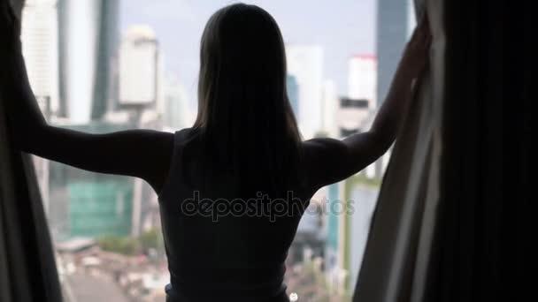 Silueta ženy odhalení záclony a při pohledu z okna. Město mrakodrapů krajina mimo