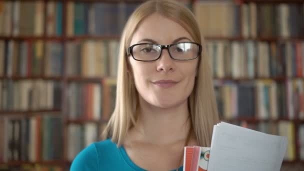 Portrait of cheerful student in glasses standing in library. Bookcase bookshelves in background
