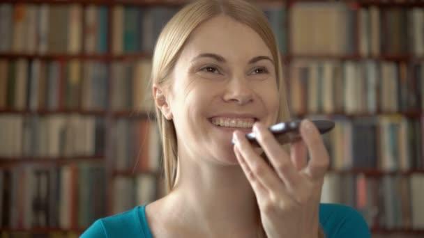 Happy usmívající se student v knihovně s použitím její smartphone, chatovat s přítelem směje