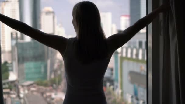 silhouet van de vrouw onthulling gordijnen en kijken uit het venster city wolkenkrabbers landschap buiten