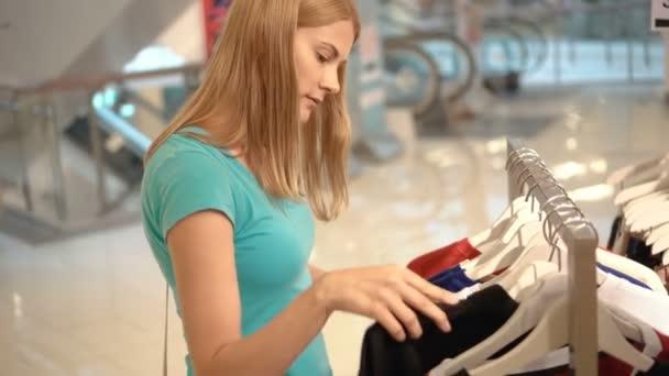 Mladá atraktivní žena výběr oblečení v obchodě. Nakupovat v obchoďáku, prodejní doba. Konzumerismus koncept