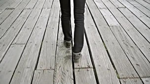 Junge Frau allein zu Fuß auf einem Holzsteg oder Brücke über Fluss, Point Of View Perspektive