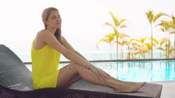 Nagyon álmodozó fiatal nő sárga ruhában, fekvő szolárium, türkizkék víz medence közelében