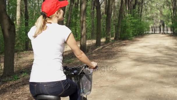 Happy aktivní sportovní mladá žena v červené čepici cyklické prostřednictvím sunny park na léta den. Zpomalený pohyb