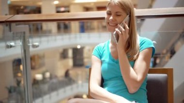 Woman sitting in shopping mall square using smartphone, using her smartphone, talking to friend