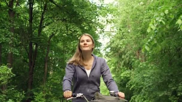 Slow Motion Happy aktivní sportovní mladá žena v Mikiny cyklické prostřednictvím sunny park na léta den