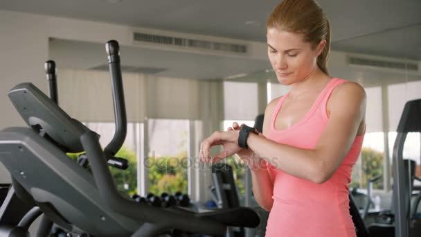 Fit active sportive žena dělá cvičení na velosimulator. Pomocí její smartwatch kontrola vitální funkce