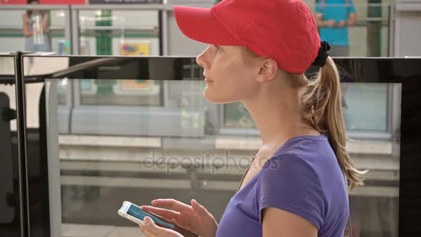 Atraktivní mladá žena na nadzemní metro stanice metra kontrola její telefon čekání vlak dorazí
