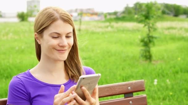Slow Motion Frau SMS auf dem Handy im Park. Verwenden ihr Smartphone messaging mit Freund durchsuchen