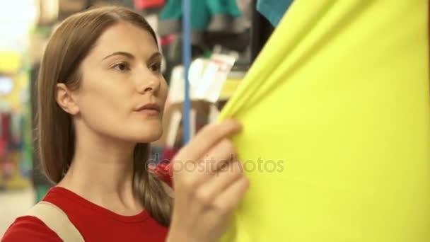 Happy atraktivní žena v červené tričko nakupovat v obchoďáku nákup oblečení. Koncept shopaholism konzumerismu