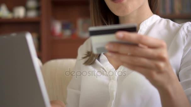Üzletasszony, fehér blúz, ülő kanapé a nappaliban vásárol online-val hiteletek kártya, laptop