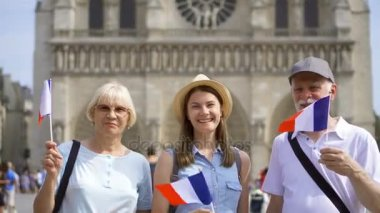 Happy family enjoying vacation. Seniors and their daughter near Notre Dame of Paris. Waving French flags