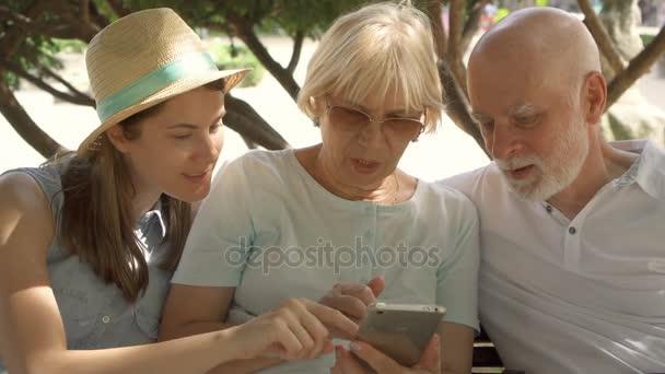 Šťastná rodina těší dovolenou. Senioři a jejich dcera sedí v parku procházení v smartphone